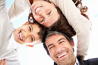Portrait of happy mature parents with son huddling up against white background