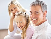 Portrait of cute young girl sitting with her parents and smiling