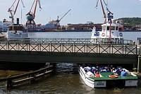 A sightseeing boat passing under a low bridge, Gothenburg, Sweden.