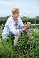 portrait of blond woman sitting in on meadow