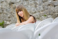 Young woman is sitting in an empty open air theater