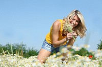 blond woman walking through fields picking wild flowers