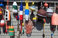 Group of buoys on facade made of shingles at fishing shack at Peggys Cove, Nova Scotia, Canada