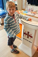 6 year old boy putting money in a lifeboat RNLI charity box in Aldeburgh, Suffolk, England, Great Britain, Uk