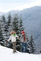 Couple holding hands and walking on remote snowy hillside