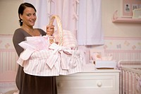 Pregnant woman holding basket of baby clothes