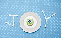 Teaspoons and plate with cupcake spelling joy on tablecloth