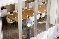 Businessman holding paperwork and looking out conference room window