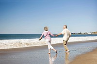 Senior couple holding hands and playing in surf at beach