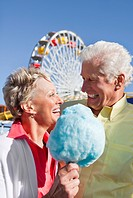 Smiling senior couple sharing cotton candy at amusement park