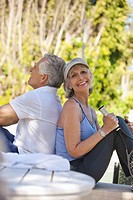 Smiling senior couple with tennis racket sitting back to back