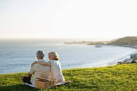 Senior couple with picnic basket on grassy hill overlooking ocean
