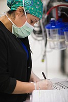 Nurse writing in medical chart in operating room