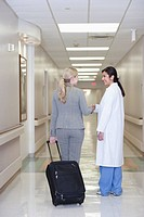 Patient with suitcase talking to doctor in hospital hallway