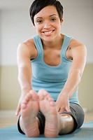 Mixed race woman sitting and stretching on exercise mat