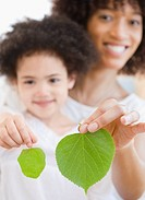 Mother and daughter holding green leaves