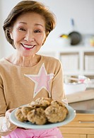 Japanese woman holding plate of cookies