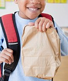 African American boy wearing backpack holding bag lunch