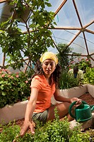 Ecuadorian woman holding watering can in greenhouse
