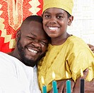 African American father hugging son in traditional clothing
