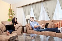 Couple sitting in living room using laptops