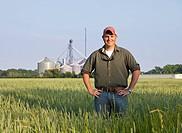 Proud Caucasian farmer posing in field