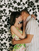 Couple kissing in front of wallpaper