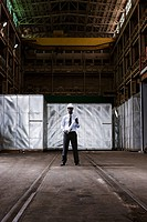 Businessman in warehouse with blueprint and hard hat