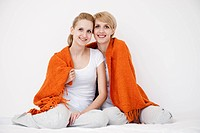 Women wrapped up on blanket sitting on b