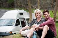 Couple relaxing with mobile home