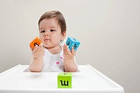 Baby boy sitting in highchair with wooden alphabet blocks