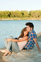 Young couple sitting near lake