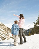 Woman and boy looking at snowy mountains
