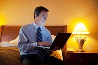 Businessman on Laptop in Hotel Room