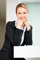 Business woman sits with hands on chin