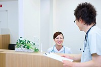 Female nurse and doctor talking at reception desk in hospital