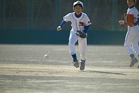 Boy in baseball uniform trying to catch a ball