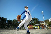 Boy in baseball team throwing ball