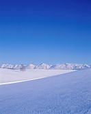Blue Sky Over a Mountain Range and a Snowy Field. Hokkaido, Japan