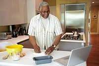 Man looking up a recipe on his laptop