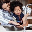 Mother and son washing in the kitchen sink