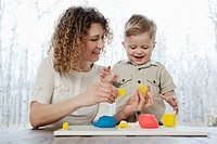 Woman playing with colored clay with toddler son