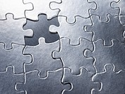 Silver jigsaw puzzle with missing piece