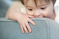 Baby chewing on back of chair (thumbnail)