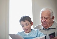 Grandfather reading book with grandson (thumbnail)
