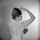 Rear view of young woman using deodorant