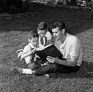 Father with twin sons reading book sitting on lawn