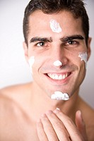 Young man applying facial cream
