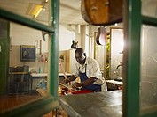 Black lute maker working in workshop