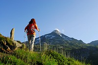 Woman hiking, mount Rauchkofel in background, Ahrntal, Zillertal Alps, South Tyrol, Italy